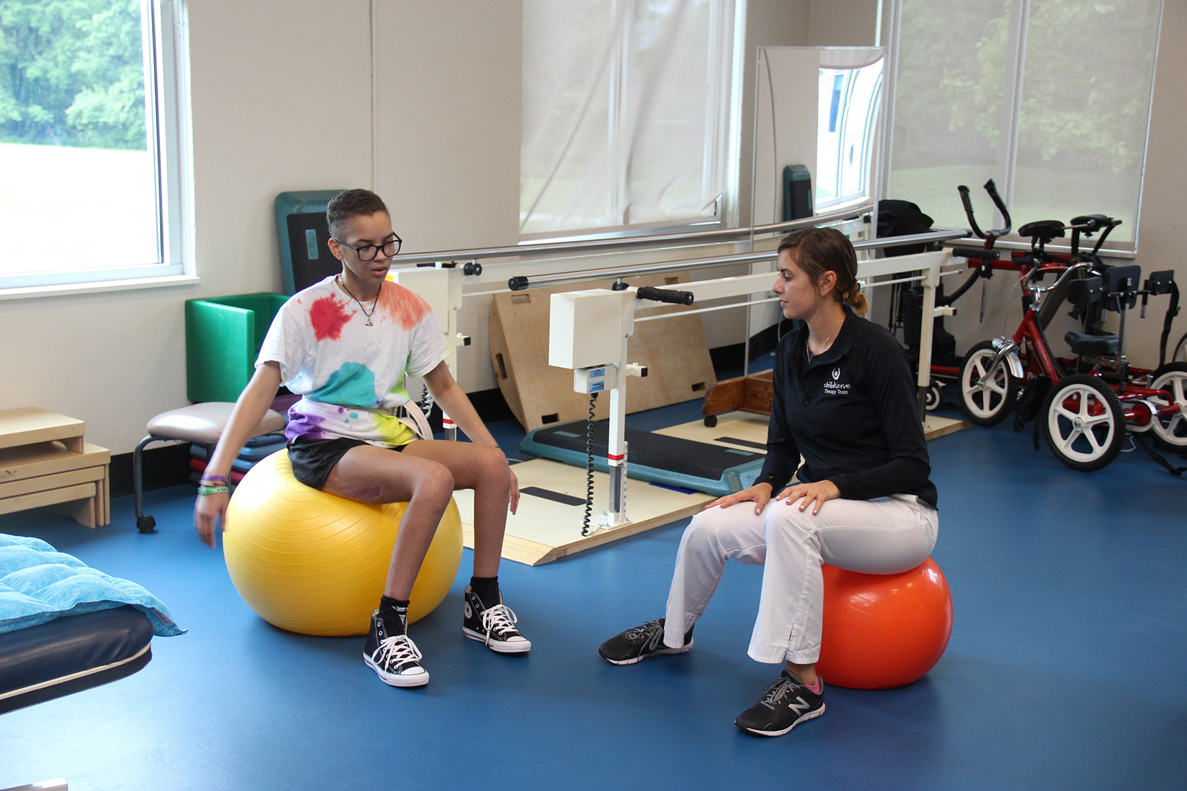 Sarah in therapy session sitting on a yellow ball.