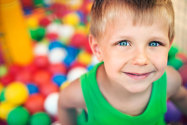 Child smiling in a ball pit.