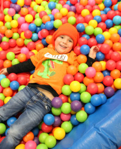 Child laying in a ball pit.