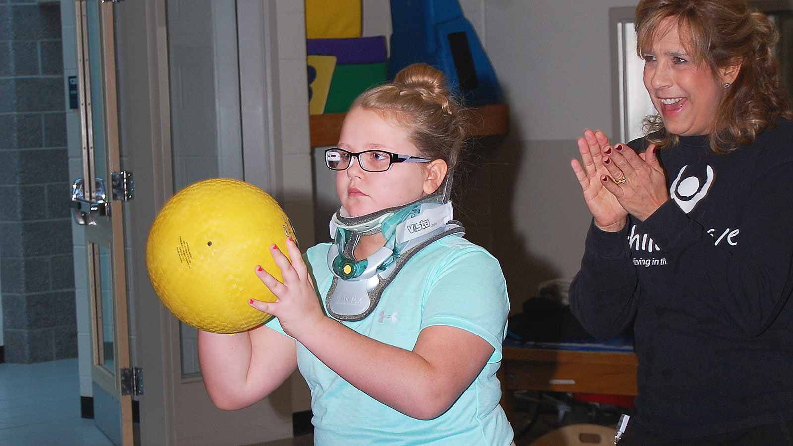 Gracen in Physical Therapy bouncing a yellow ball.