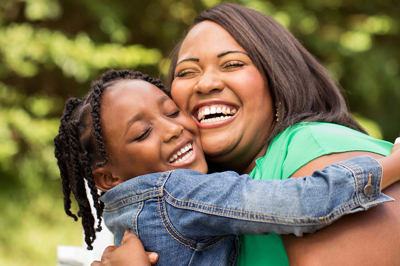 Mom smiling, hugging her child.