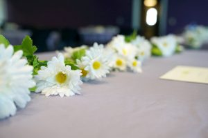 White daisy flowers laying on a table for the DIASY Award celebration.