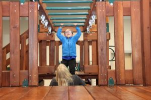Bennett doing monkey bars in occupational therapy